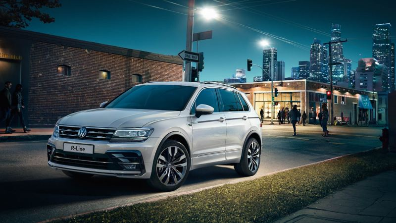 A Volkswagen Tiguan parked in the city at night, lit sky scrappers in the background.