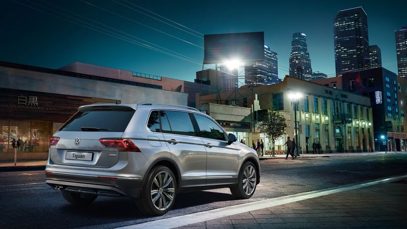 A Volkswagen Tiguan parked on the street at night, the city skyline in the distance.