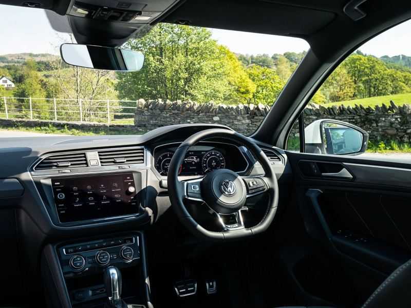 A Volkswagen Tiguan's interior with the driver's seat, steering wheel, dashboard and centre console