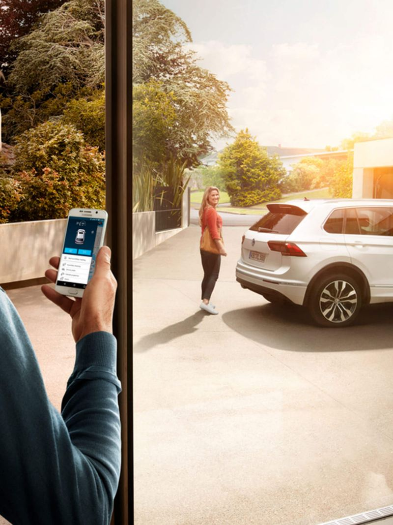 A man using the Volkswagen Car-Net App Connect on his phone while his wife is standing near their Tiguan