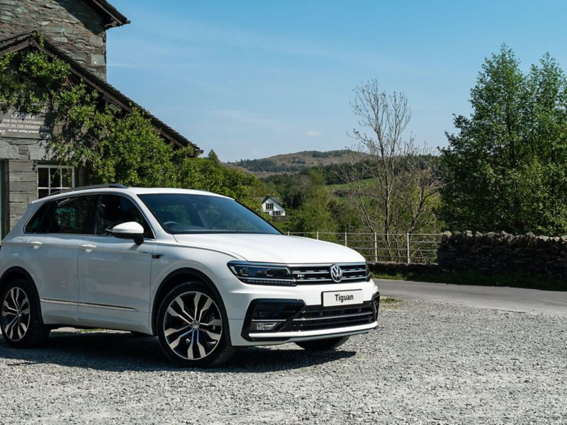 A white Volkswagen Tiguan parked in front of a cottage in the mountains