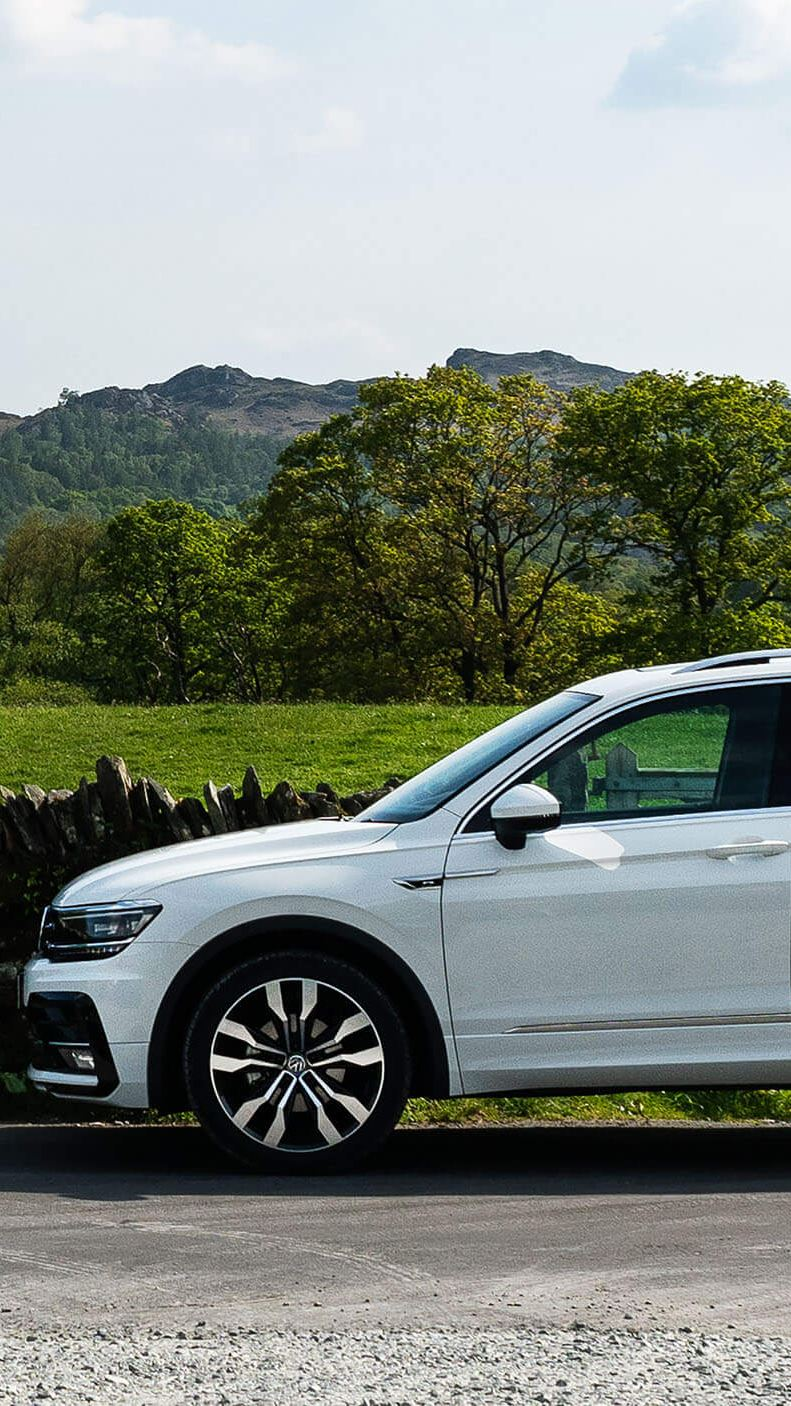 A white Tiguan parked near a lake in the mountains