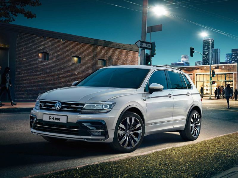 A Tiguan parked in a street at night.