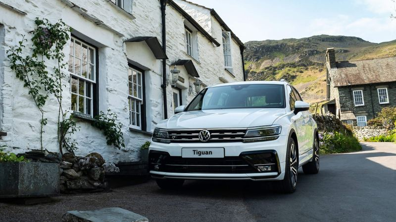A white Volkswagen Tiguan parked in front of houseson a very steep village street.