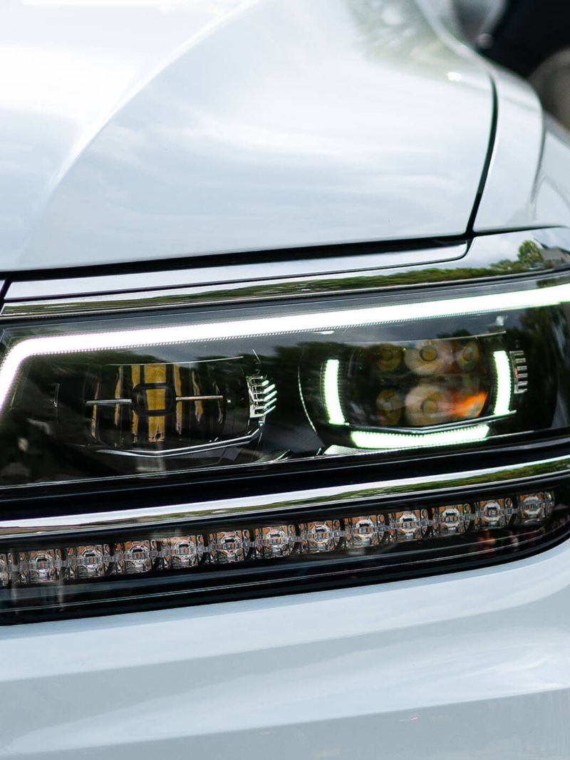 Headlights of a white Volkswagen Tiguan