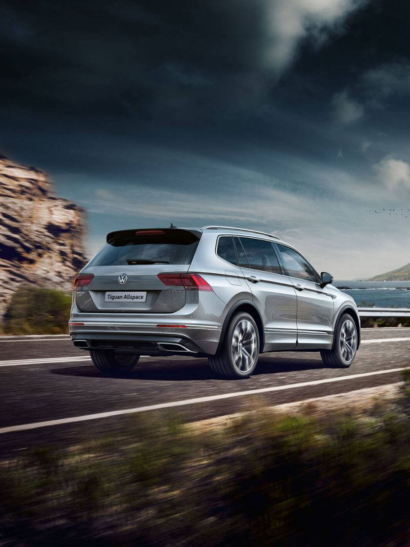 A silver Tiguan Allspace driving on the road near mountains and a lake