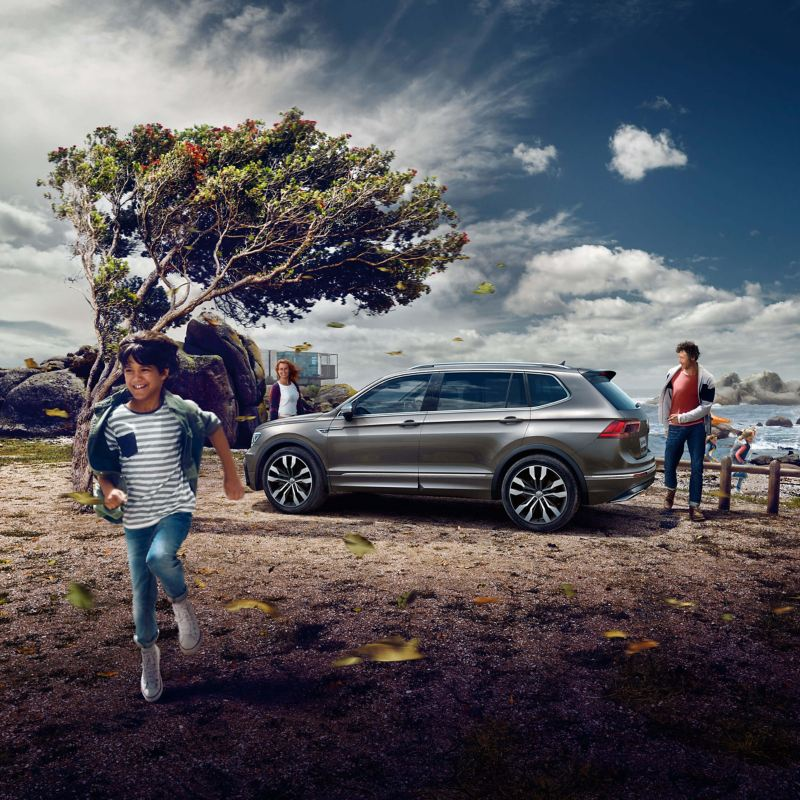 A silver Volkswagen Tiguan Allspace with a family on holidays near the beach