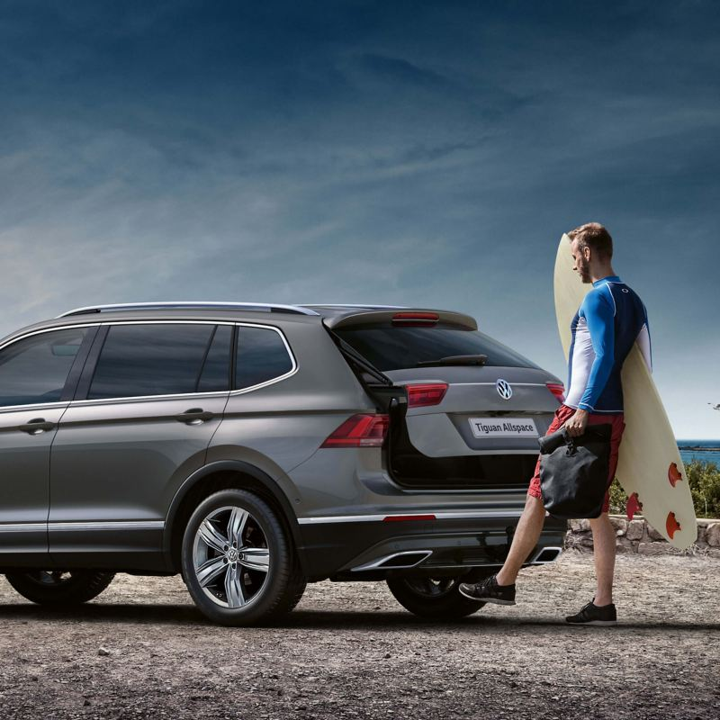 A man opening the boot of a silver Volkswagen Tiguan Allspace while parked near the beach