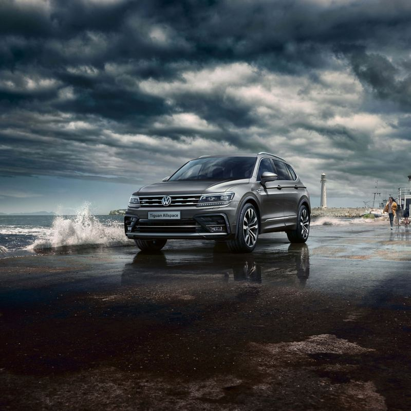 A dark grey Volkswagen Tiguan Allspace driving near the beach