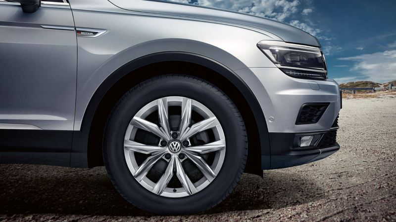 10-spoke alloy wheel and headlight of a silver Volkswagen Tiguan Allspace