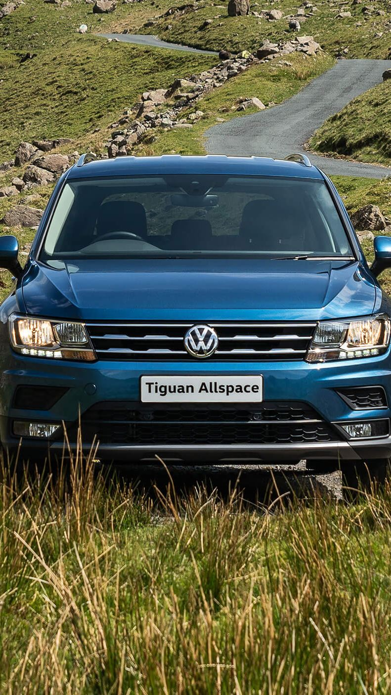 A bkue Tiguan Allspace in the countryside, parked a mountain road.