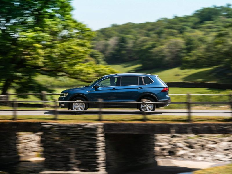 A blue Volkswagen Tiguan Allspace driving on country roads