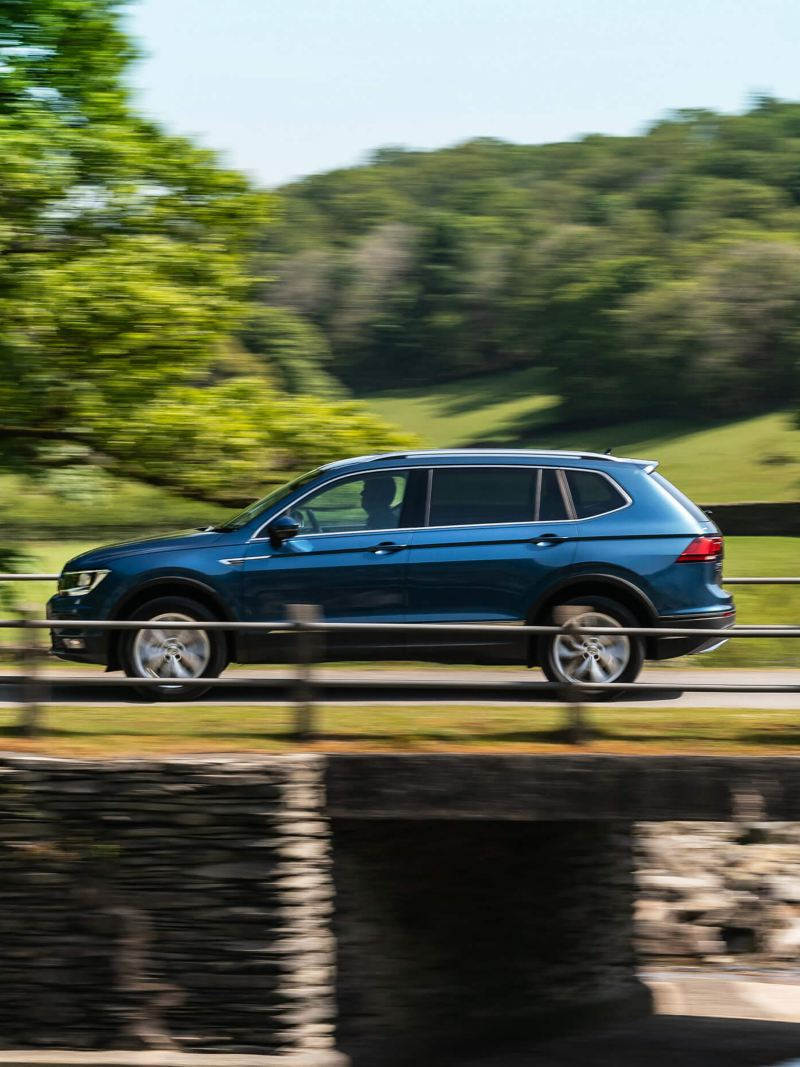 A blue Volkswagen Tiguan Allspace, driving across a countryside bridge.