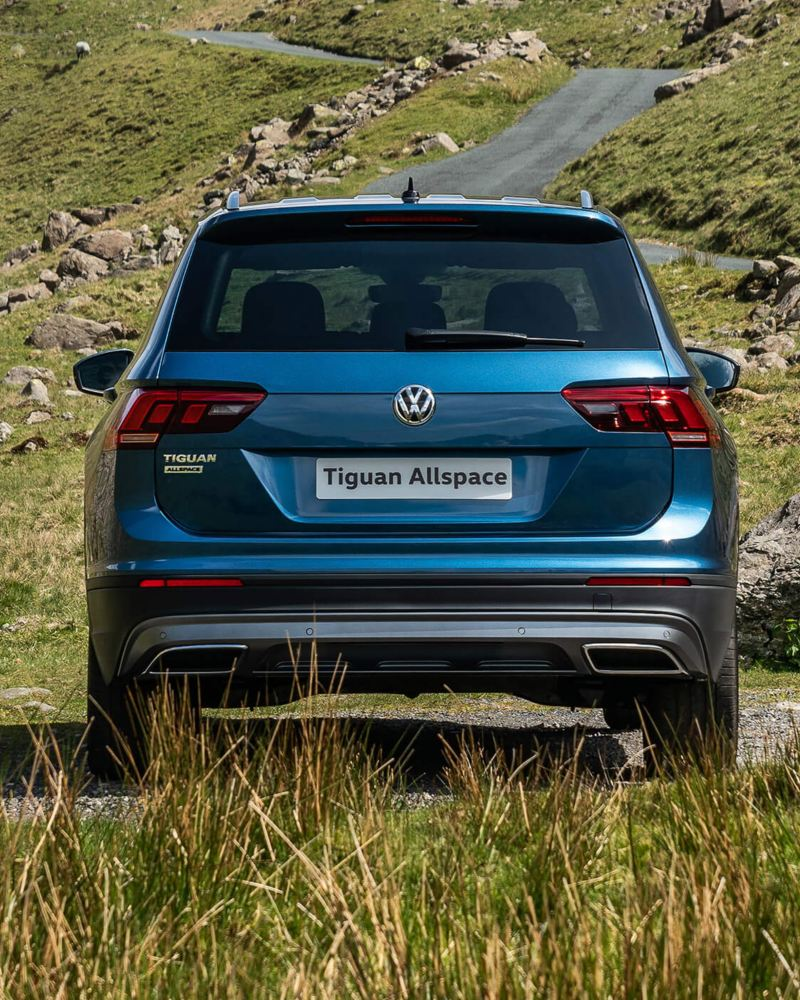 Rear view of a a blue Tiguan Allspace that is parked near country roads