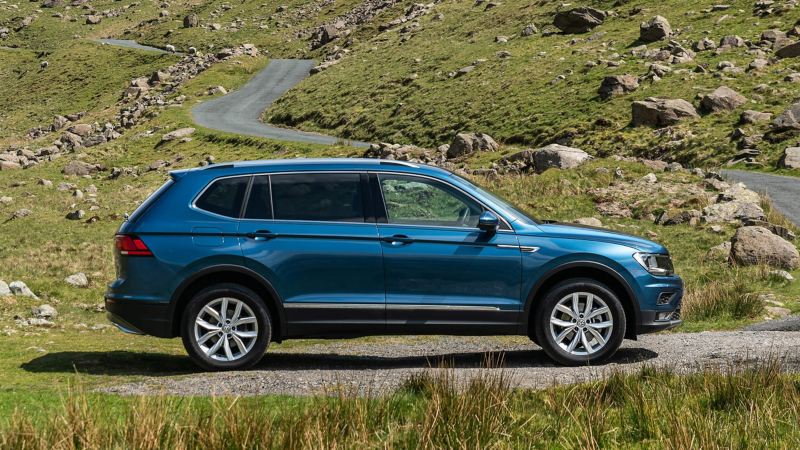 Side profile of a blue Tiguan Allspace parked near country roads