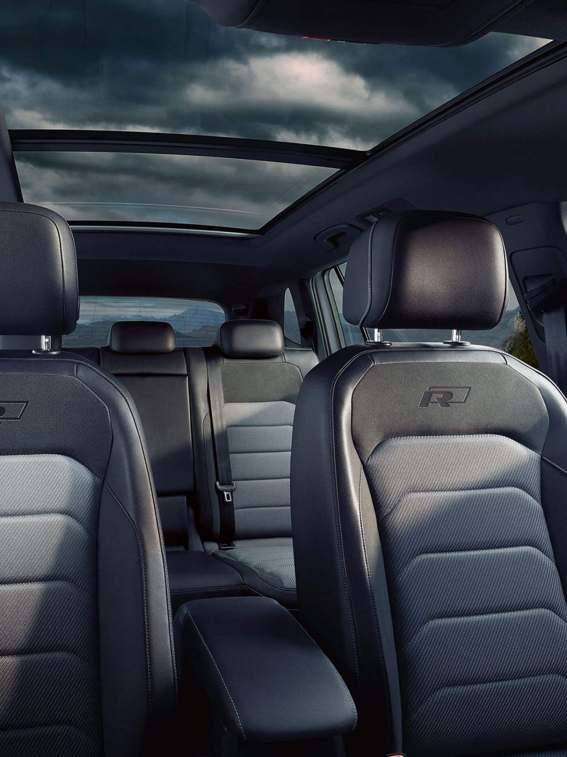 Interior shot of a Tiguan Allspace, a storm mountain terrain visible outside.