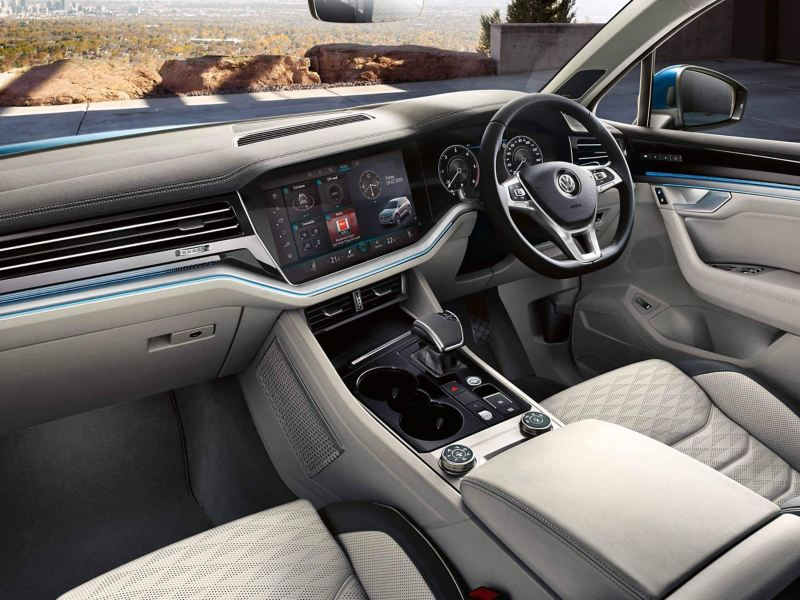 the interior of a Volkswagen Touareg, focusing on the sterring wheel and centre console with the touchscreen.