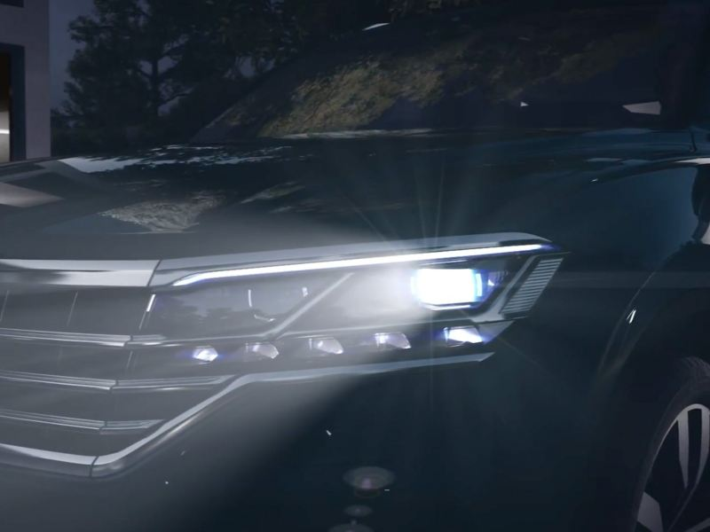 Full beam headlight close-up of a Volkswagen SUV.