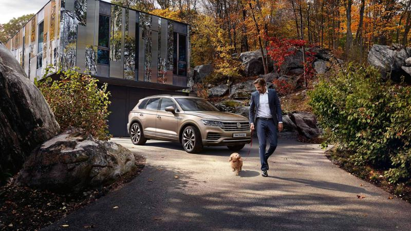 A man walking his dog next to a bronze Volkswagen Touareg, a glass front house in the background.