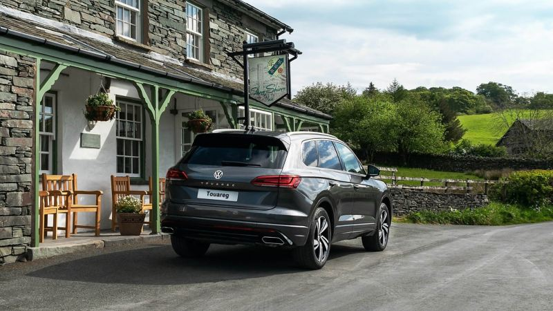 A volkswagen Touareg next to a country pub, fields in the background.