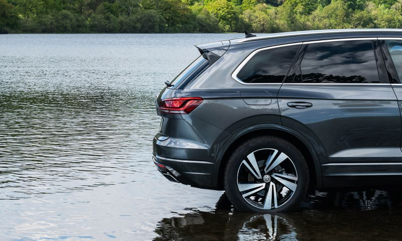 The rear side of a Volkswagen Touareg parking near a lake.