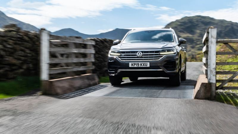 The Volkswagen Touareg, driving across a cattle-grid in the countryside.