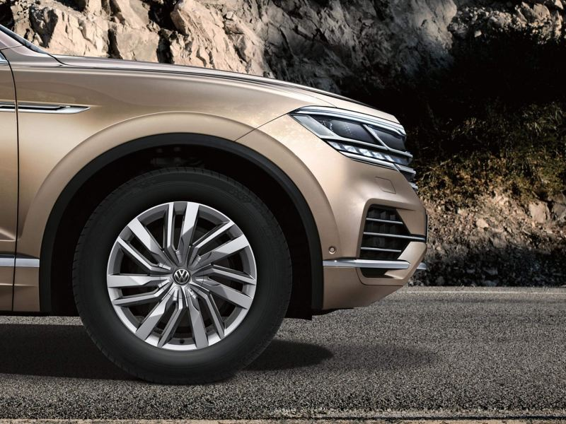 Front profile shot of a bronze Volkswagen Touareg, on a mountain road.