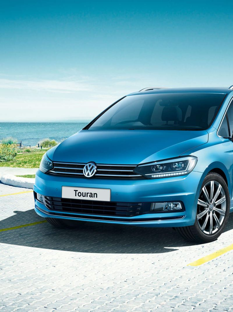 A blue Volkswagen Touran parked in front of a building near the sea