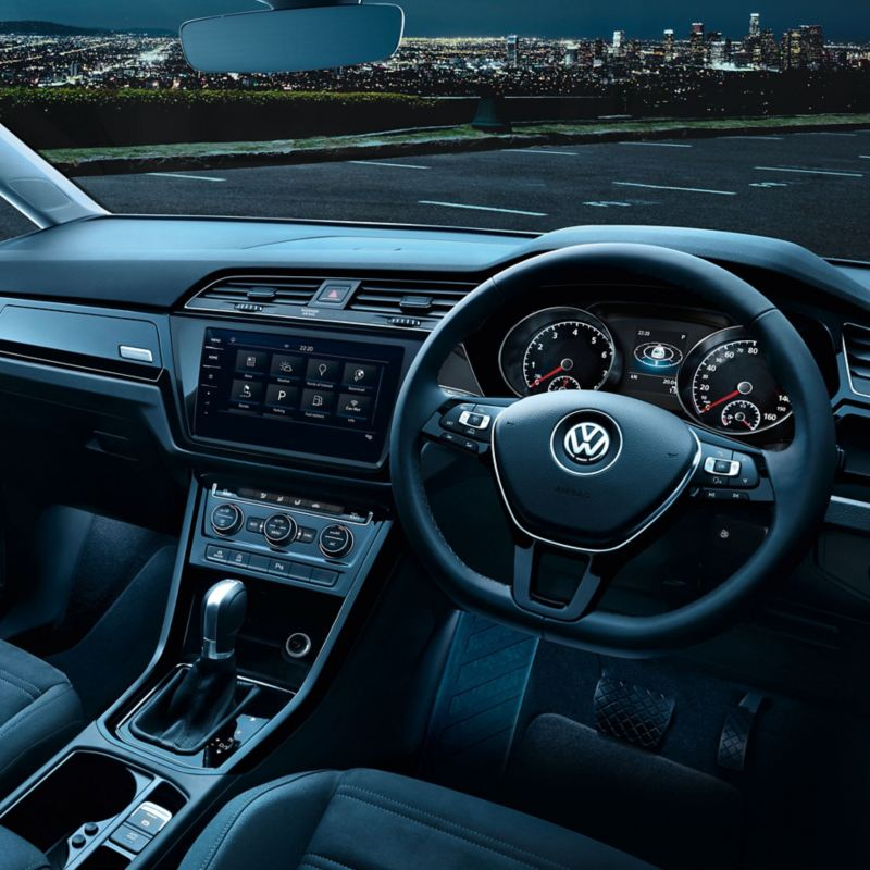 The interior of a Volkswagen Touran showing the steering wheel, dashboard, gearstick and the centre console with the touchscreen