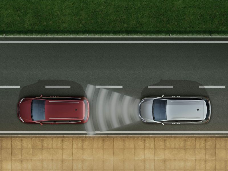 A silver Volkswagen Sharan driving behind a red Volkswagen Sharan with sound waves that represent the Front Assist