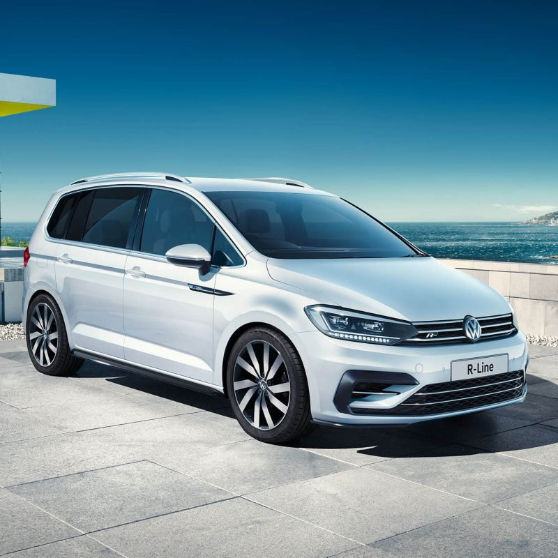 A white Volkswagen Touran parked in front of a building near the sea