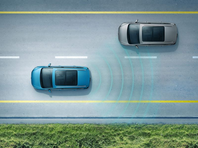 A blue Volkswagen Touran driving on the road with the Lane Assist in action