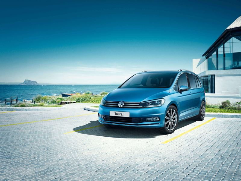 A blue Volkswagen Touran parked in front of a house near the sea