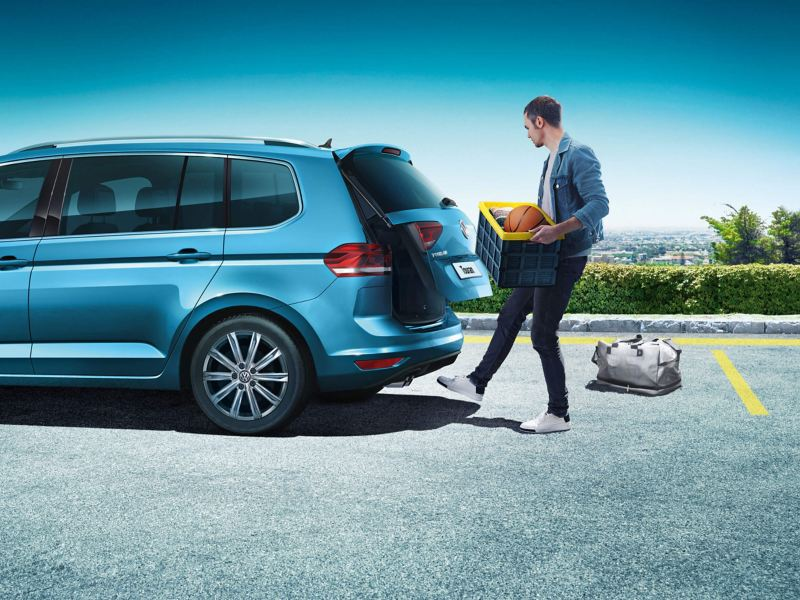 A man holding a basket full of stuff using the easy-open luggage compartment of a Volkswagen Touran with his leg
