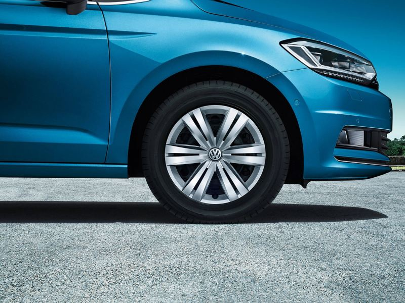 The wheel and the headlight of a blue Volkswagen Touran