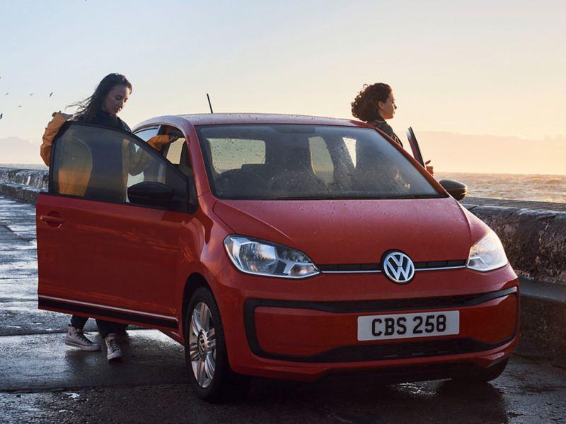 A red Volkswagen up! 3 door, on the coast.