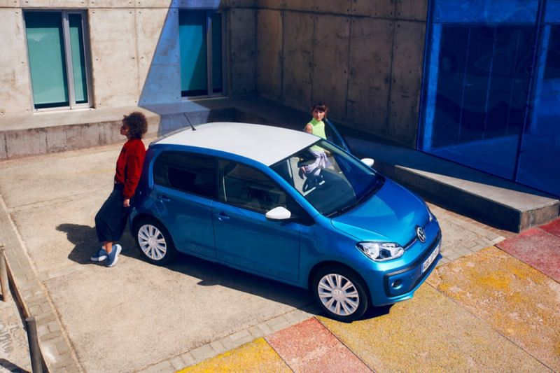 Aerial view of a parked new up! in blue with two people standing next to it