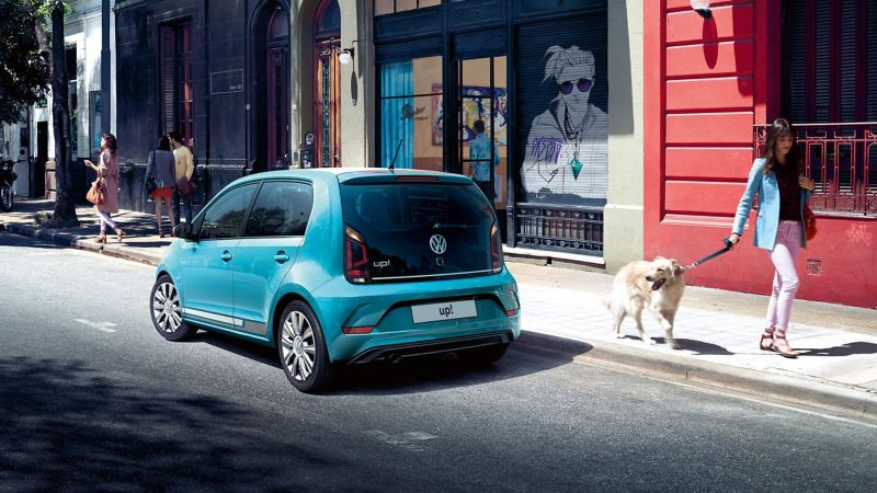 VW up! parked on a street and a lady walking past with her dog