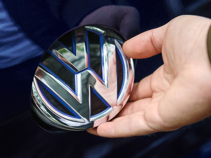 A man turning the front VW badge, where the charge plug is located behind.