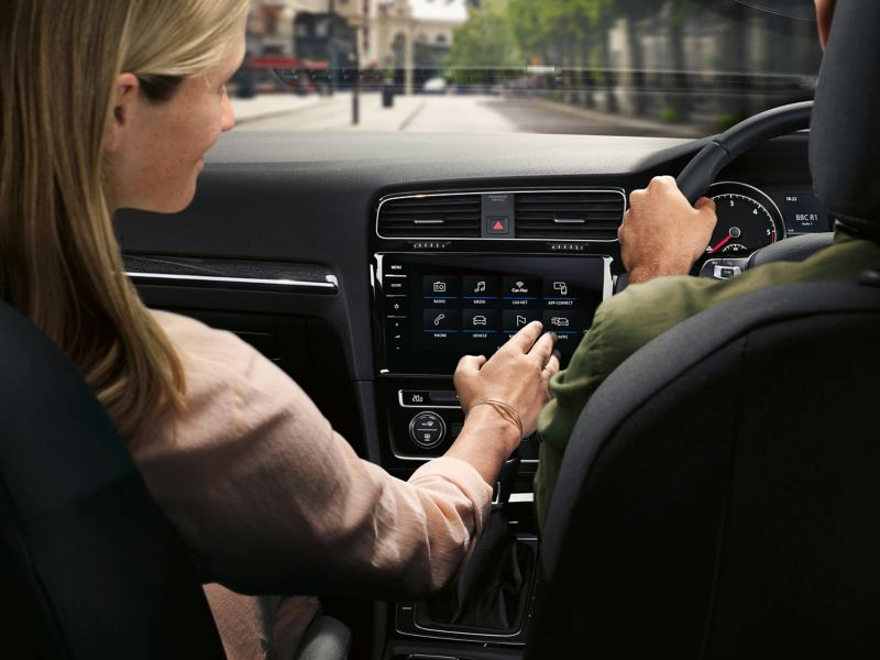 A lady using the optional mobile phone interfaces in a Volkswagen Golf Estate Alltrack.