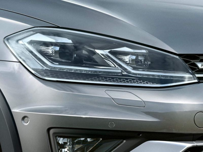 Headlight shot of a grey Volkswagen Golf Estate Alltrack.