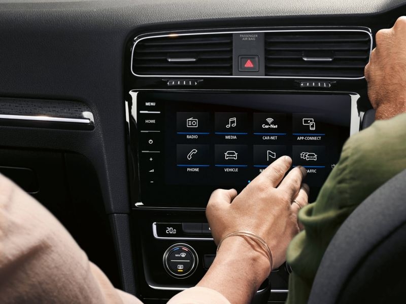 Interior shot of a lady using Car-Net system on the central screen,  in a Volkswagen Golf Estate Alltrack.