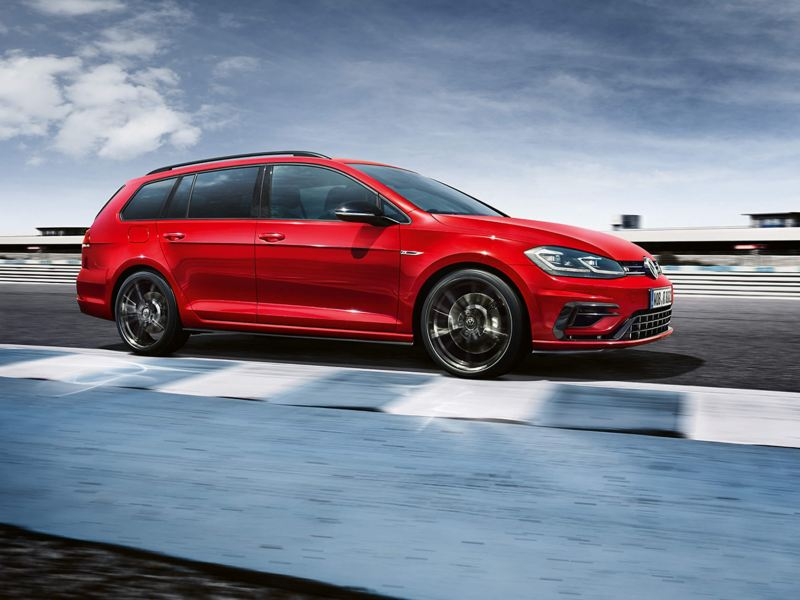 A profile shot of red Volkswagen Golf Estate R driving on a race track.