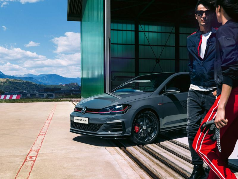 Two men talking next to a gunmetal grey Golf GTI