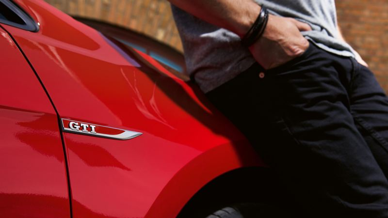 Man leaning on the side of a red Golf GTI.