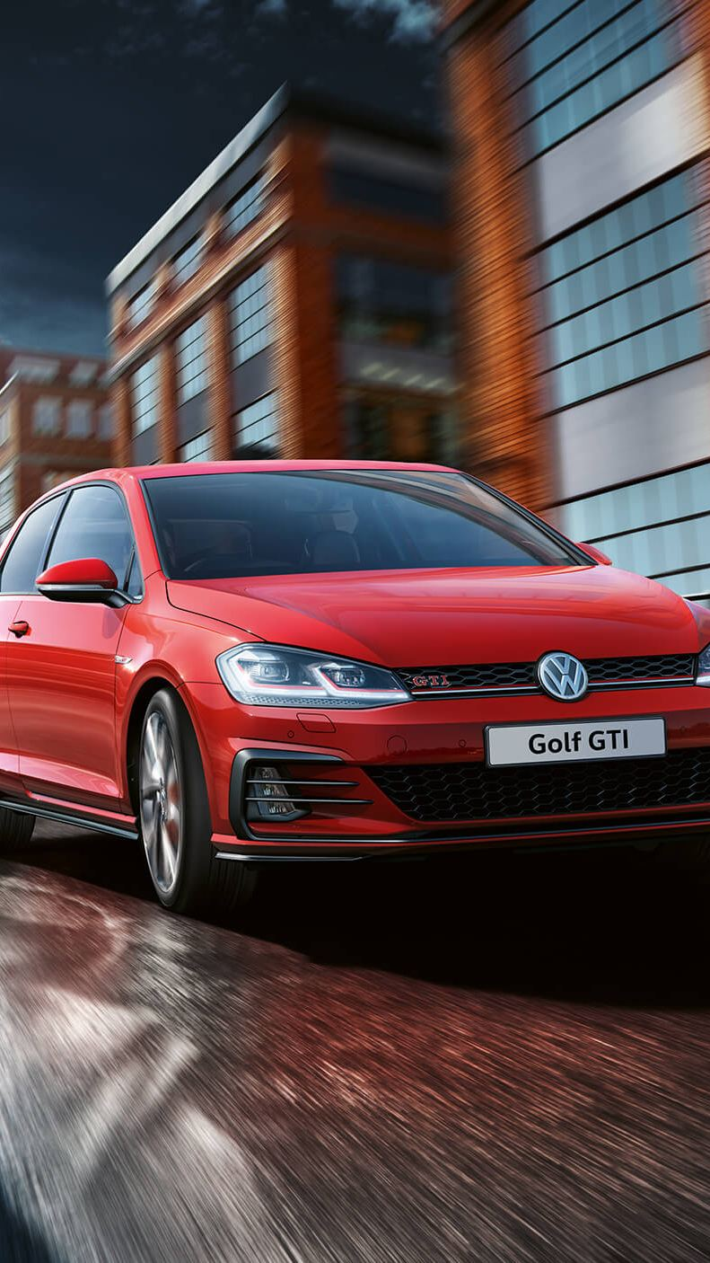 Red Golf GTI driving through streets