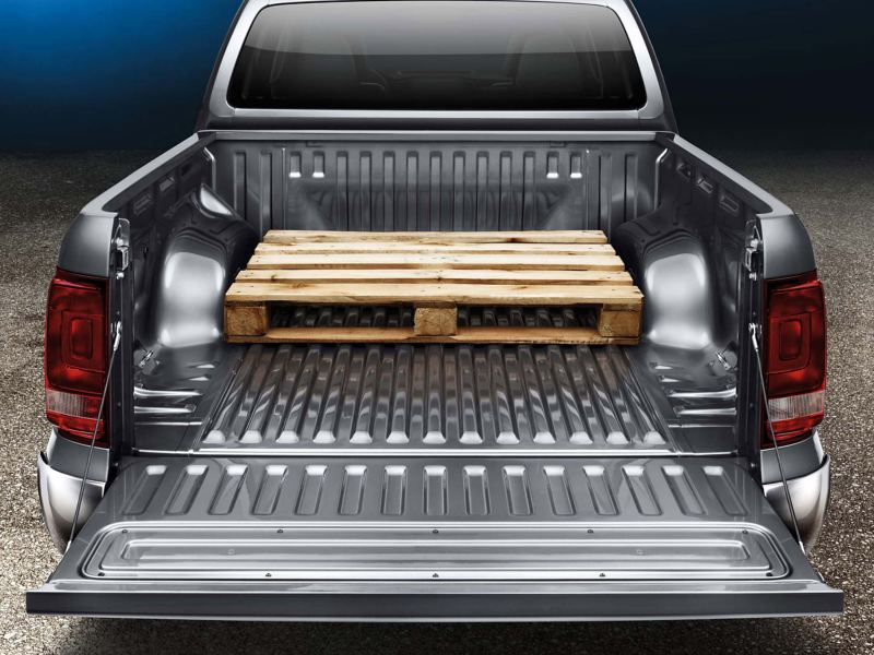 Open back of a Grey VW Amarok pick-up with wooden crate loaded