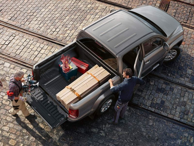 Two men loading rear of Amarok pick-up