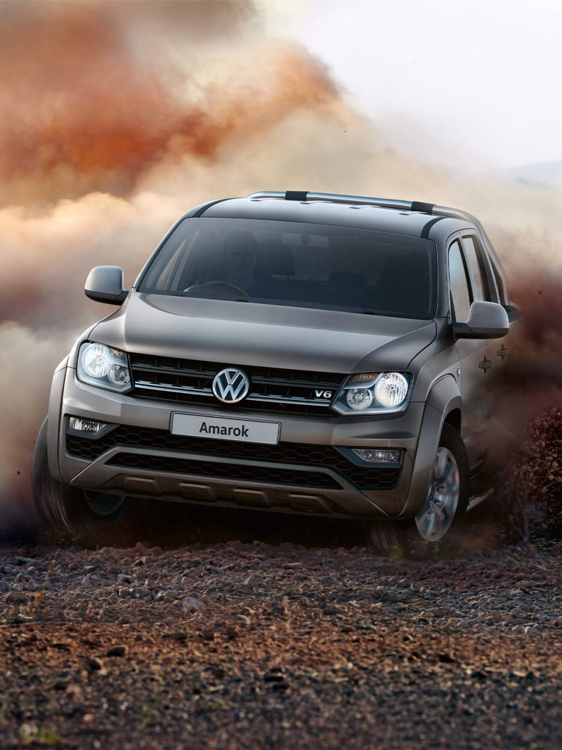 Amarok driving at an angle on dirt road with dust under wheels