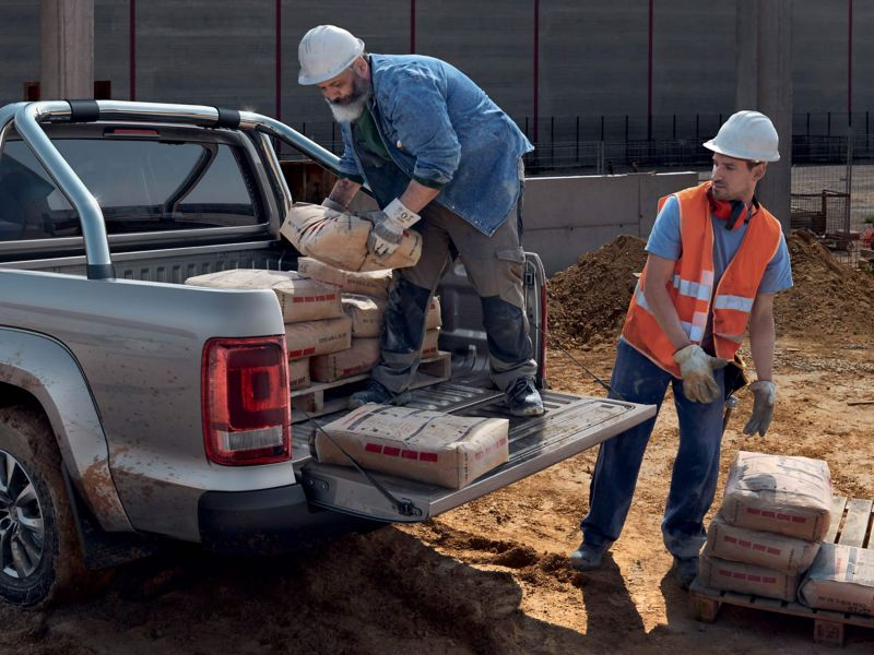 Two men in hard hats rear loading an Amarok pick-up